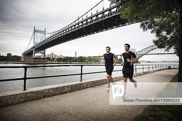 Freunde rennen auf der Promenade gegen die Triborough-Brücke
