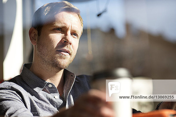 Man with coffee cup looking away while sitting in cafe seen through glass