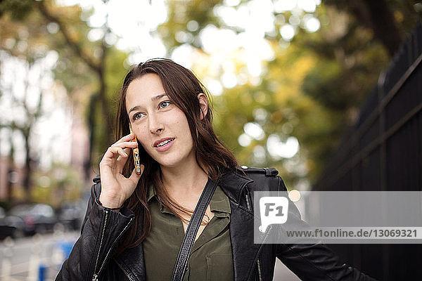 Frau telefoniert  während sie am Zaun steht