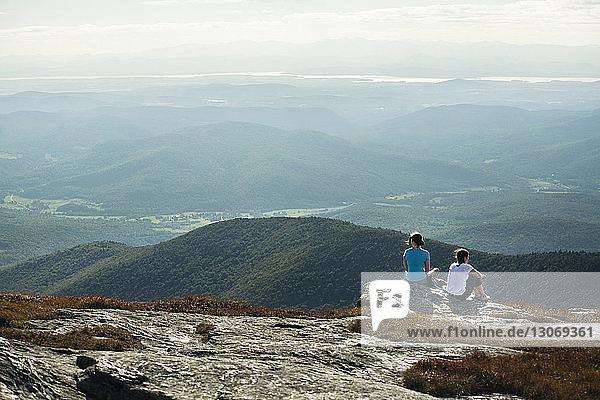 Rückansicht von Freunden  die auf einer Klippe vor Bergen sitzen