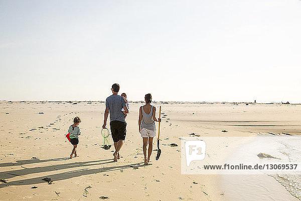 Rückansicht einer Familie  die bei klarem Himmel am Strand spazieren geht