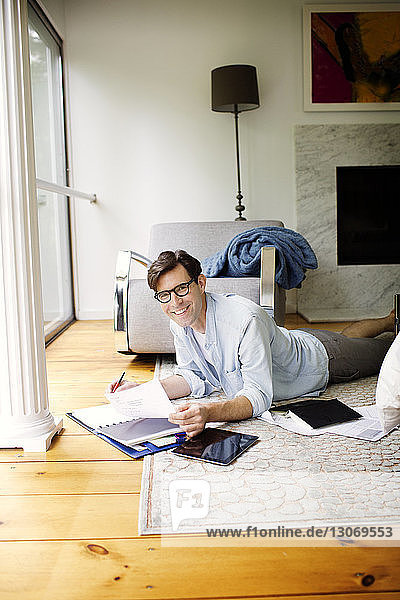 Smiling man doing paperwork by tablet computer while lying on floor at home