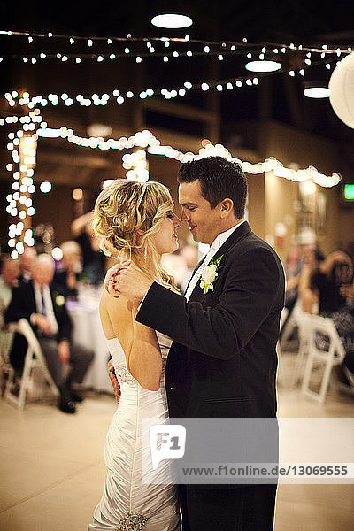Bride and groom dancing in illuminated room during wedding