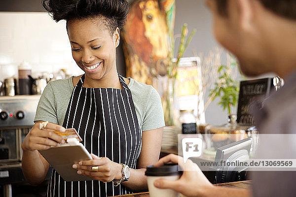 Besitzer liest Debitkarte  während der Kunde im Café am Schalter steht