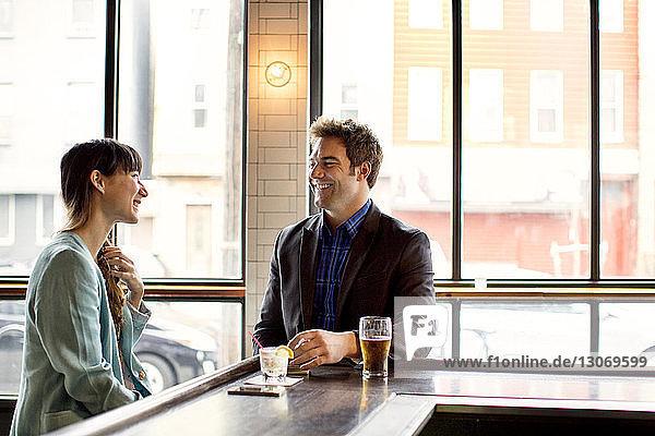 Lächelnde Freunde unterhalten sich  während sie in der Bar sitzen