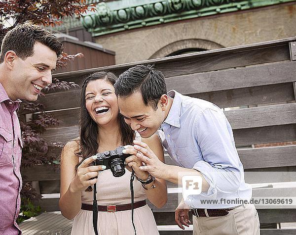 Glückliche Freunde schauen in die Kamera  während sie an einer Holzwand stehen