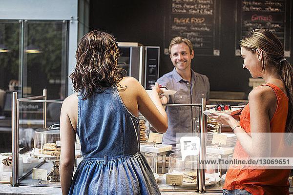 Besitzer serviert Kunden im Café ein Dessert