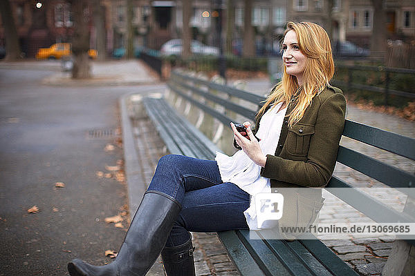 Woman with mobile phone looking away while sitting on bench