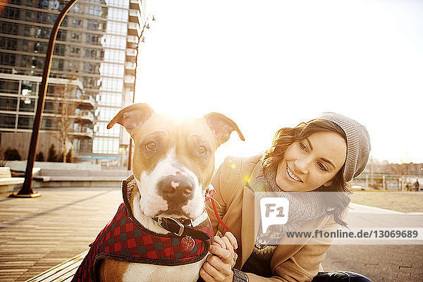 Woman looking at dog while sitting on bench against clear sky