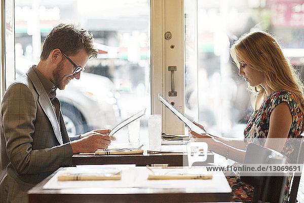 Seitenansicht des Paares beim Lesen der Speisekarte  während es im Restaurant sitzt
