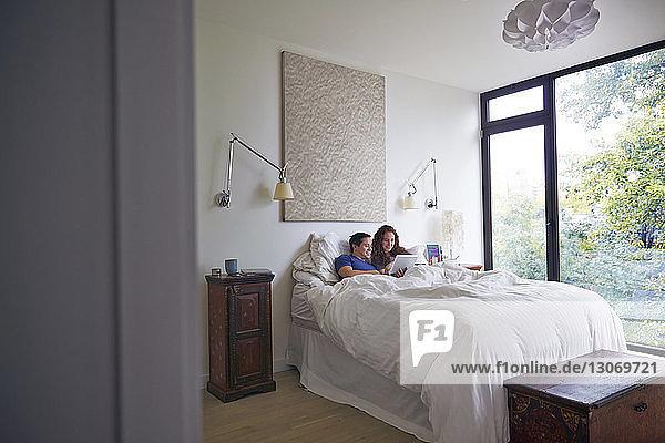Ehepaar benutzt Tablet-Computer  während es zu Hause im Bett liegt
