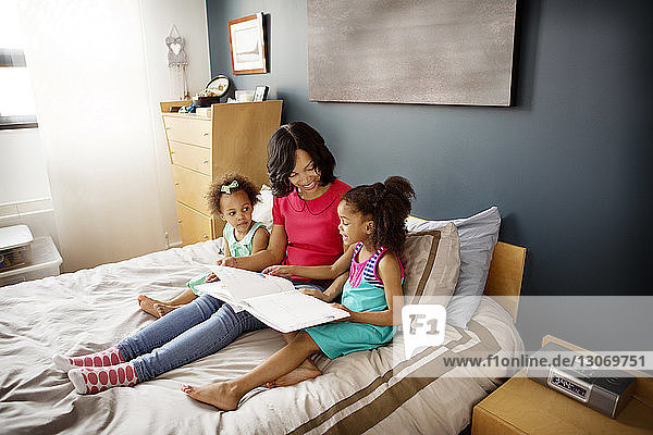 Girl showing book to mother and sister while resting on bed at home