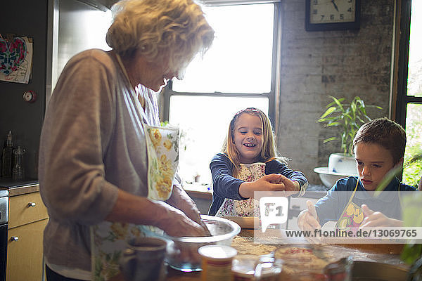 Happy children with grandmother mixing flour in kitchen