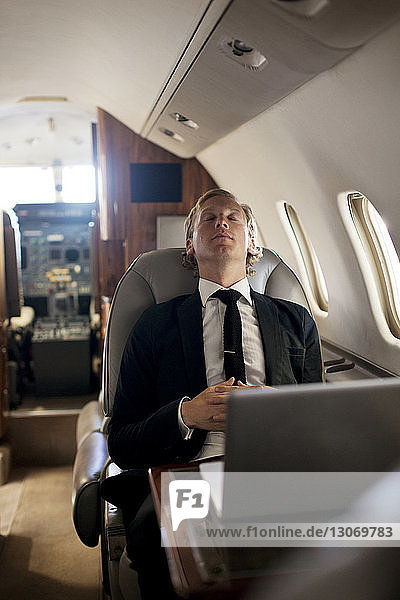 Businessman relaxing in airplane