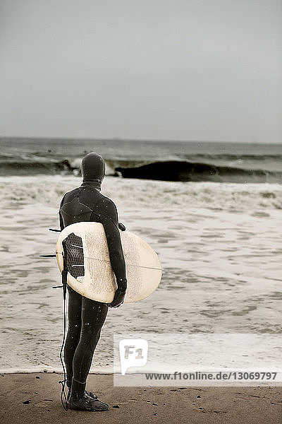 Rear view of man carrying surfboard while standing at beach