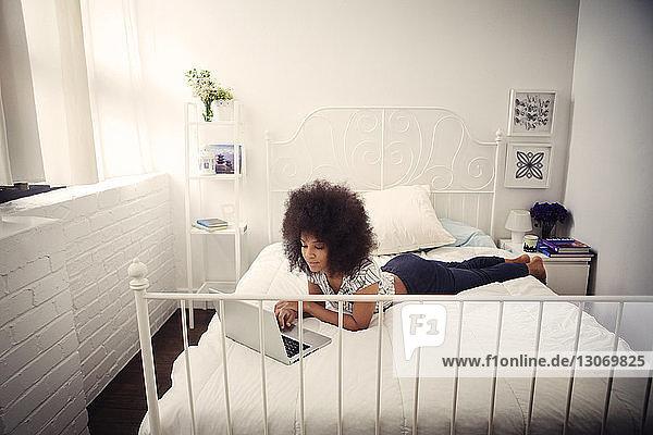 Frau in voller Länge mit Laptop-Computer  während sie zu Hause auf dem Bett liegt