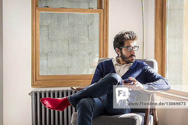 Man looking away while sitting on chair at home