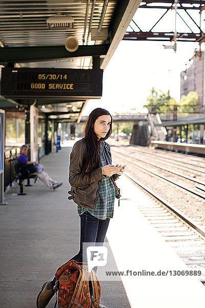 Frau schaut weg  während sie auf dem Bahnsteig steht