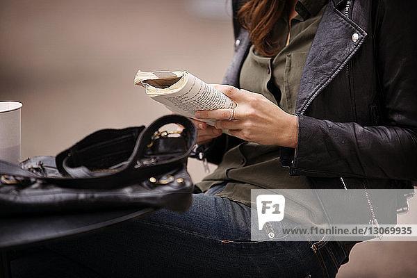Mittelteil einer Frau  die am Tisch sitzend ein Buch liest