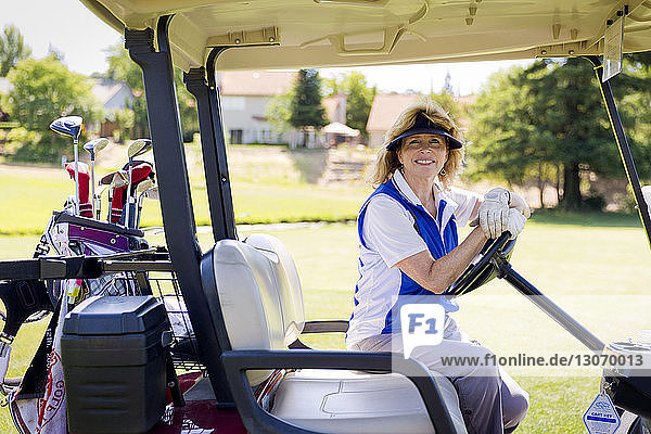 Portrait of happy woman sitting in golf cart