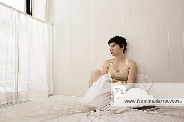 Frau mit der Hand im Haar  die einen Laptop benutzt  während sie zu Hause auf dem Sofa sitzt