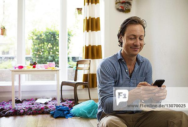 Glücklicher Mann benutzt Mobiltelefon zu Hause