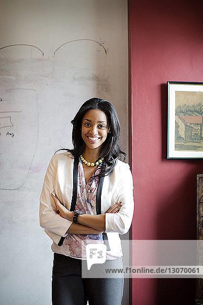 Porträt einer Geschäftsfrau  die im Amt an der Wand steht