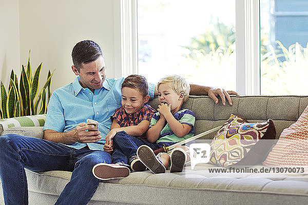 Man sitting with sons on sofa while looking at mobile phone
