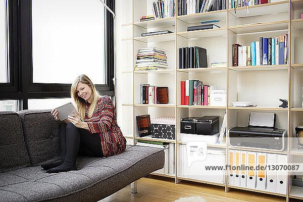 Frau benutzt Tablet-Computer  während sie zu Hause auf dem Sofa sitzt