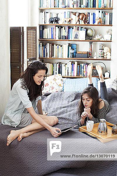 Hochwinkelansicht der Schwestern beim Blick auf den Tablet-Computer