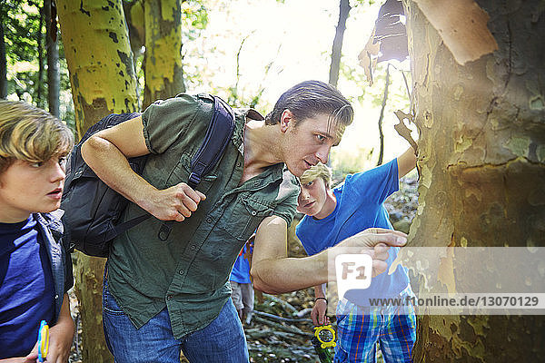 Teacher with children examining tree bark in forest