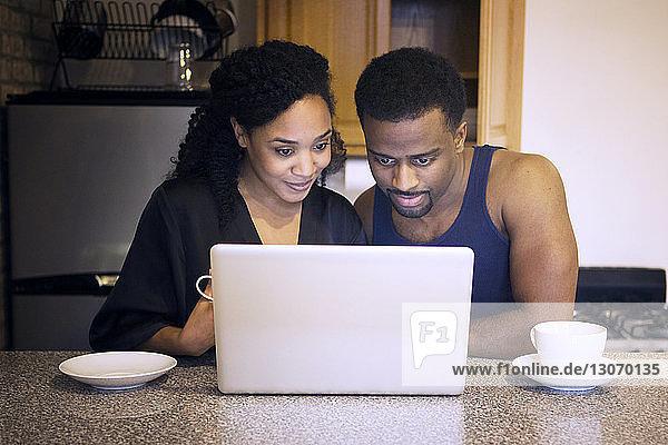 Ehepaar betrachtet Laptop-Computer in der Küche