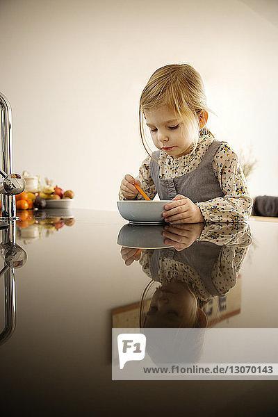 Mädchen hält Schüssel und Löffel  während sie zu Hause am Tisch sitzt