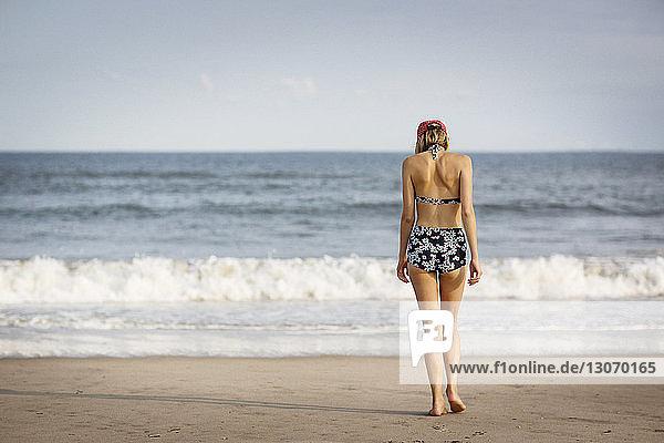 Rückansicht einer Frau  die am Strand am Ufer spazieren geht