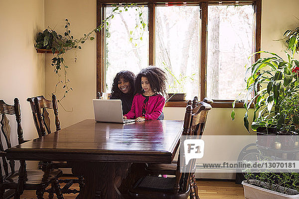 Happy mother using laptop with daughter at home
