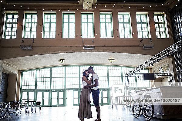 Seitenansicht eines in der Halle stehenden Liebespaares