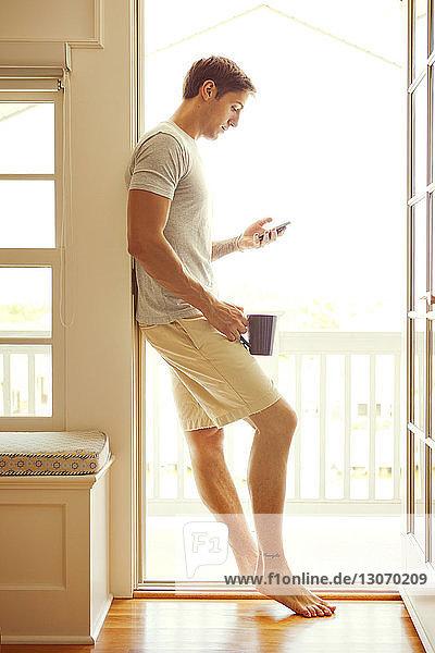 Seitenansicht eines Mannes  der ein Mobiltelefon benutzt  während er sich zu Hause an die Tür lehnt