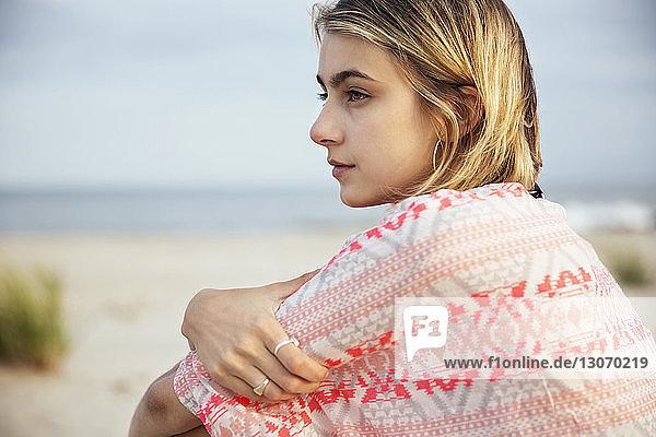 Seitenansicht einer Frau  die beim Sitzen gegen den Himmel wegschaut