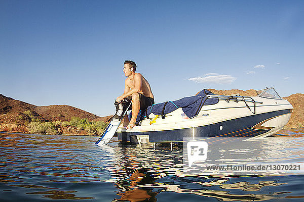 Man looking away while sitting in motorboat against sky