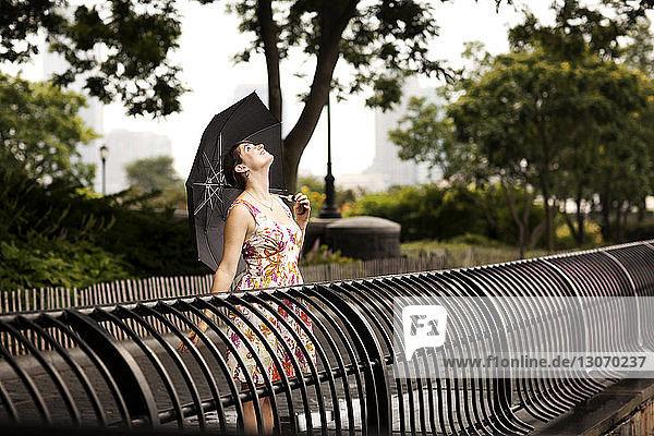 Sorglose Frau mit Regenschirm schaut auf  während sie am Geländer steht