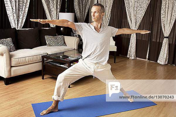 Man practicing warrior 2 yoga positing at home