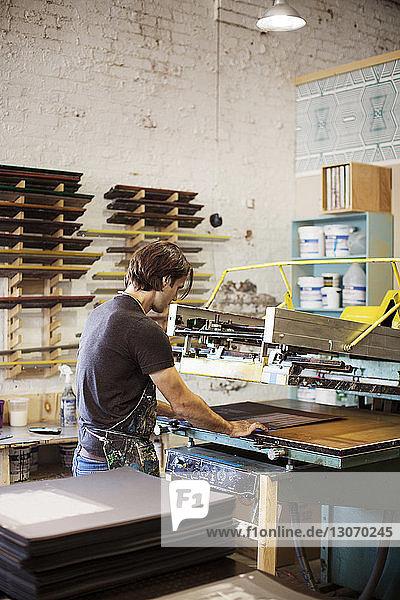 Arbeiter bei der Bedienung von Siebdruckmaschinen in der Werkstatt
