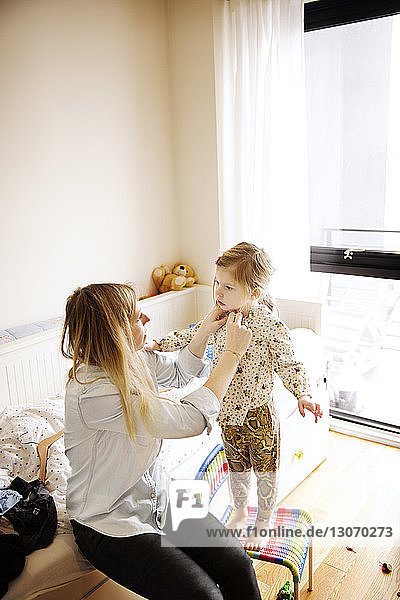 Hochwinkelaufnahme einer Mutter  die zu Hause das Kleid ihrer Tochter wechselt
