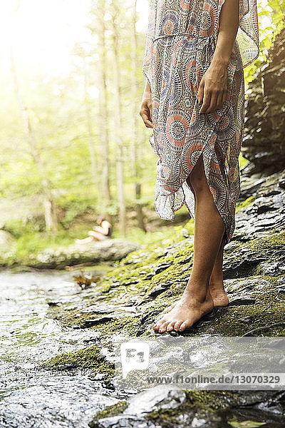 Niedriger Abschnitt einer auf Felsen stehenden Frau am Seeufer