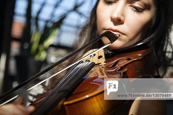 Close-up of woman playing violin at home