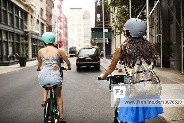 Rückansicht von Freunden  die auf der Straße in der Stadt Fahrrad fahren