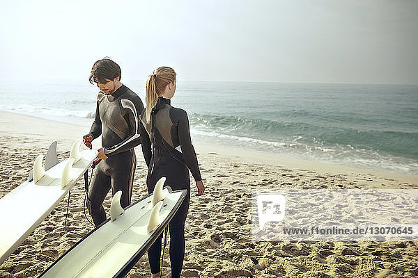 Man and woman wearing wetsuits standing by surfboards at beach