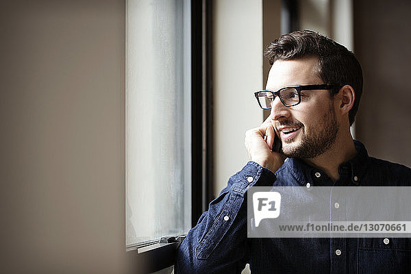 Man talking on mobile phone while standing by window at home