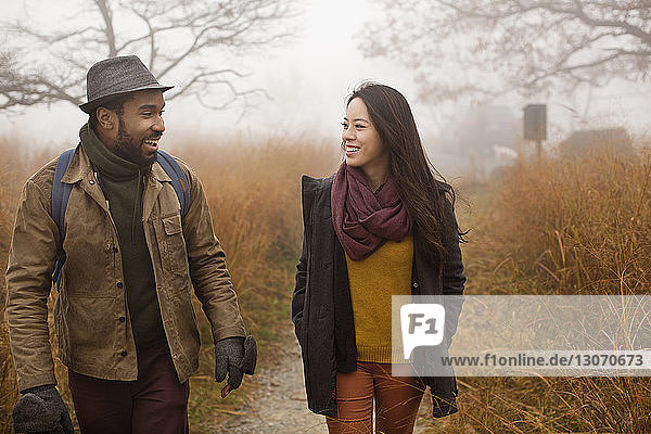Couple talking while walking in forest