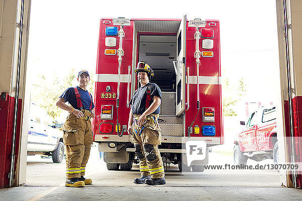 Portrait of happy fire fighters standing against fire engine